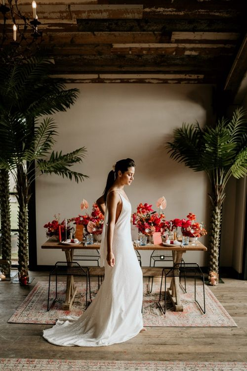 Bride in Minimalist Wedding Dress Standing in Front of a Tablescape filled with Red & Pink Wedding Flowers