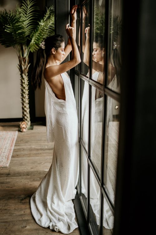 Bride in Minimalist Wedding Dress with Fringe Back Detail Standing at a Window