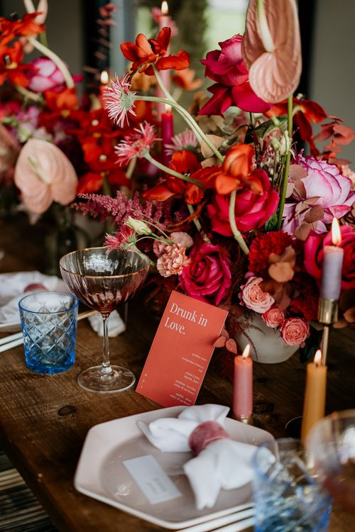 Red and Pink Floral Centrepieces with Coloured Taper Candles and Modern Wedding Stationery Design