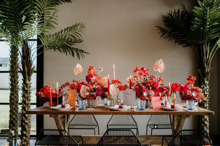Red and Pink Wedding Flower Table Decor with Taper Candles, Coloured Glasses and Modern Stationery