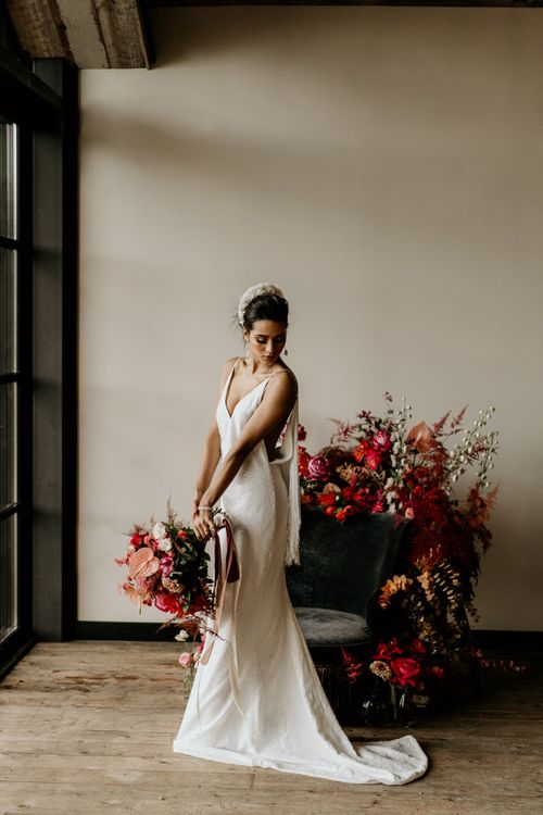 Bride in Minimalist Wedding Dress with Spaghetti Straps and White Headdress Holding a Red and Pink Tropical Bridal Bouquet