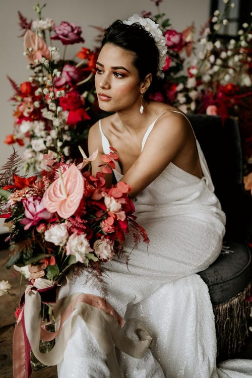 Bride in Minimalist Wedding Dress with Spaghetti Straps and White Headdress Holding a Red and Pink Bridal Bouquet