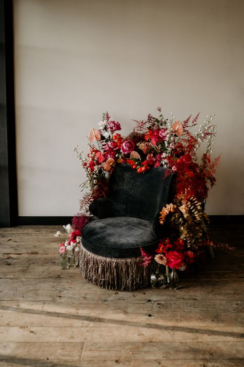 Velvet Chair Covered in Red and Pink Wedding Flowers