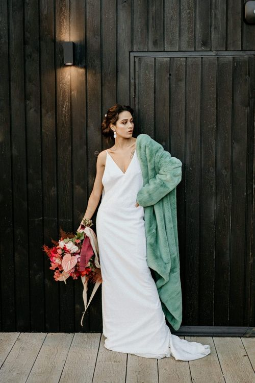 Modern Bride in Minimalist Wedding Dress and Blue Teddy Coat Holding a Pink and Red Bouquet with Anthurium Flower Stems