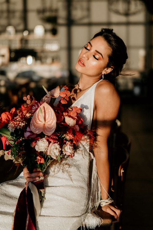Modern Bride in Minimalist Wedding Dress Holding a Red and Pink Bridal Bouquet with Anthurium Flower Stems
