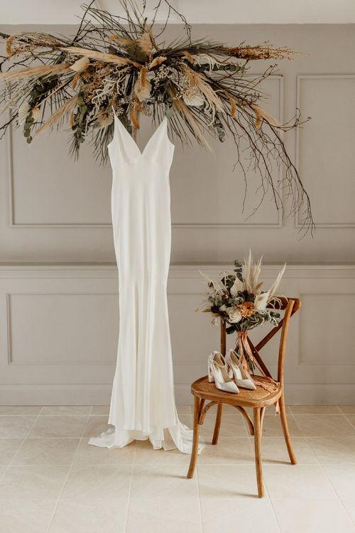 Minimalist Wedding Dress Hanging Under a Dried Flower Installation