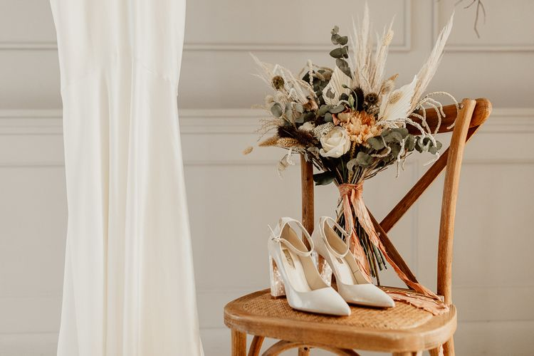 Bridal Shoes and Dried Flower Bouquet Resting on a Wooden Chair