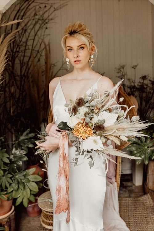 Bride holding a Dried Flower and Grasses Wedding Bouquet