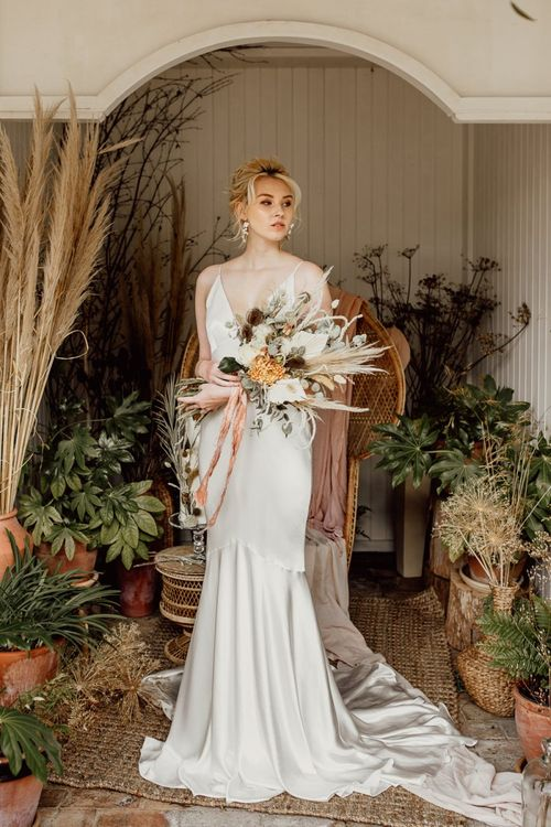 Bride in Minimalist Wedding Dress Holding a Dried Flower Wedding Bouquet Tied with Ribbon