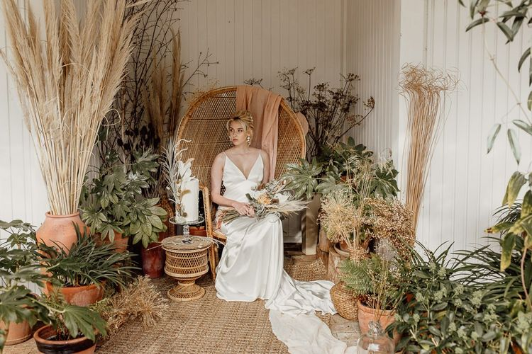 Modern Bride Sitting on a Wicker Peacock Chair Surrounded by Potted Plants