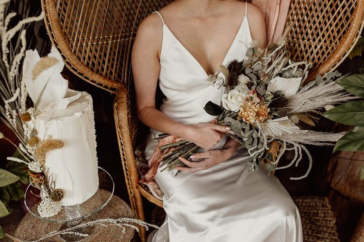 Bride in Minimalist Satin Wedding Dress Sitting on a Peacock Chair Holding Her Bouquet