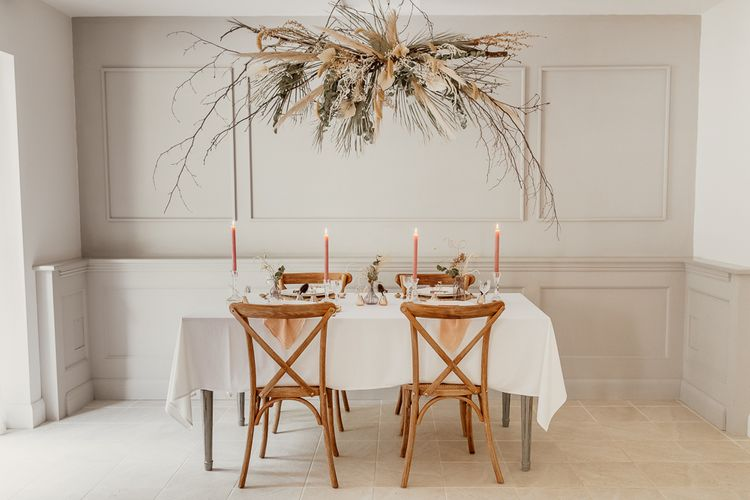 Minimalist Tablescape with Hanging Flower Installation, Wooden Chairs & Peach Taper Candles