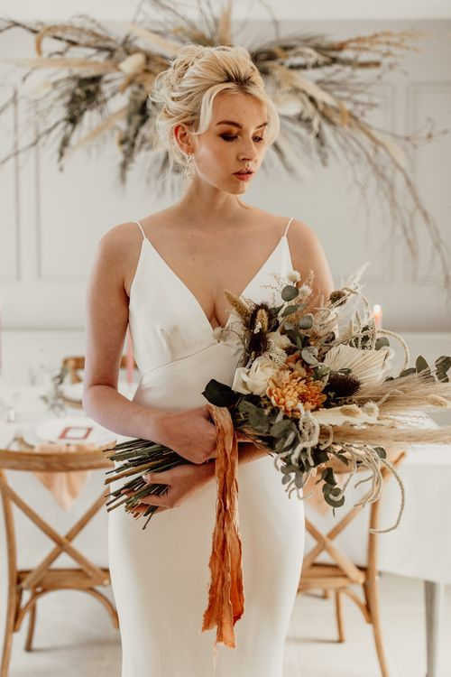 Bride in Minimalist Wedding Dress with Plunging Neckline Holding a Wedding Bouquet Tied with Ribbon