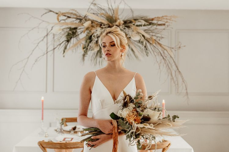 Bride in Minimalist Wedding Dress with Plunging Neckline Holding a Wedding Bouquet  of Dried Grasses, Foliage and Orange Flowers