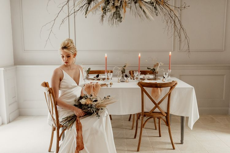 Bride in Minimalist Wedding Dress Sitting at a Tablescape with Flower Installation and Taper Candles
