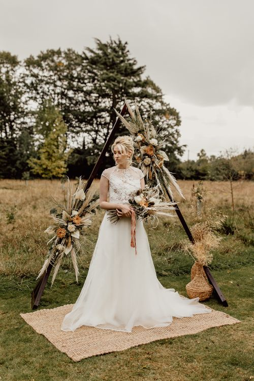 Bride in Tulle Skirt and Lace Top Wedding Dress Standing in From of a Wooden Frame Altar Decorated in Flowers