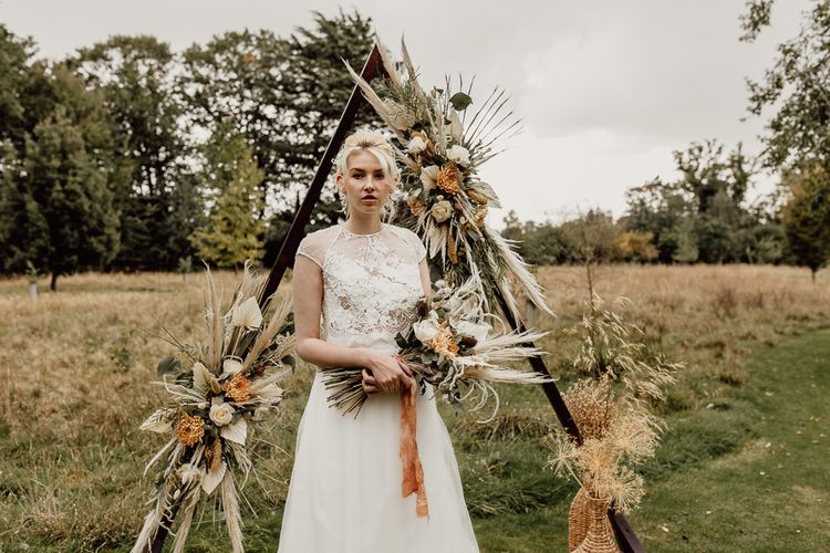 Boho Bride Standing in Front of a Triangle Frame Altar Decorated with Dried Flowers