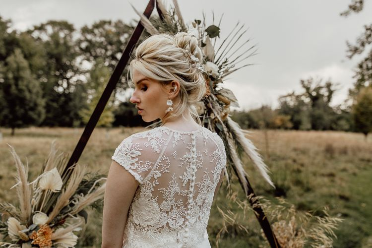 Bride in Delicate Lace Bridal Top with Buttons Down the Back and Matching Earrings and Hair Accessories