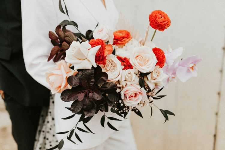 Winter wedding bouquet with red ranunculus and pink roses