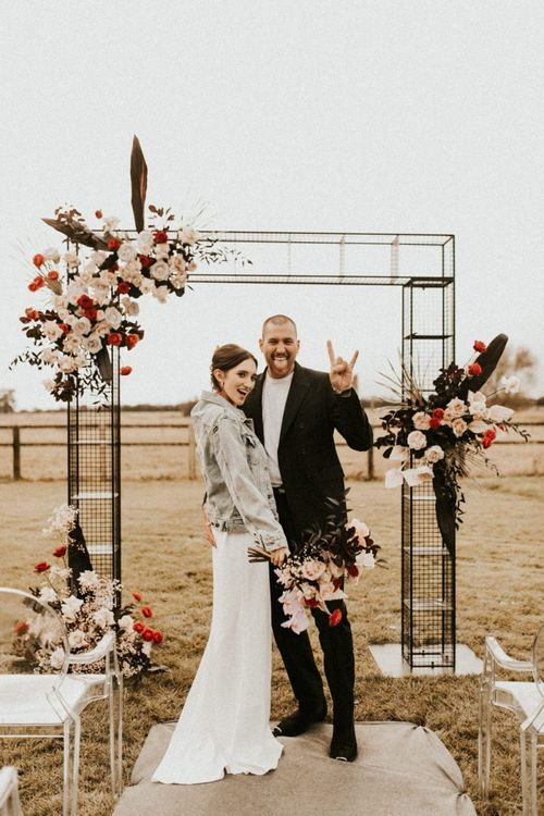 Stylish bride and groom at contemporary metal altar at Godwick Great Barn