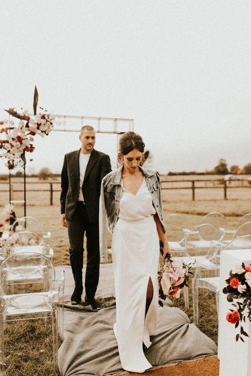 Stylish bride in fitted wedding dress with front slit and denim jacket