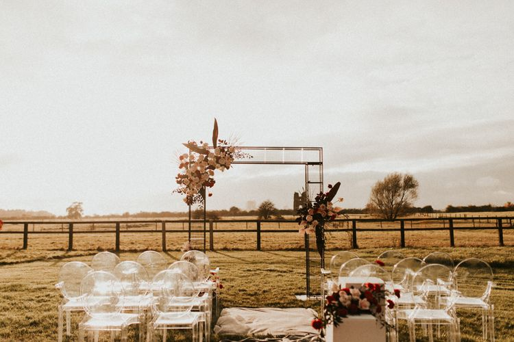 Outdoor wedding ceremony at Godwick Great Barn with wire frame altar and ghost chairs