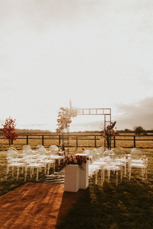 Outdoor wedding ceremony at Godwick Great Barn during golden hour
