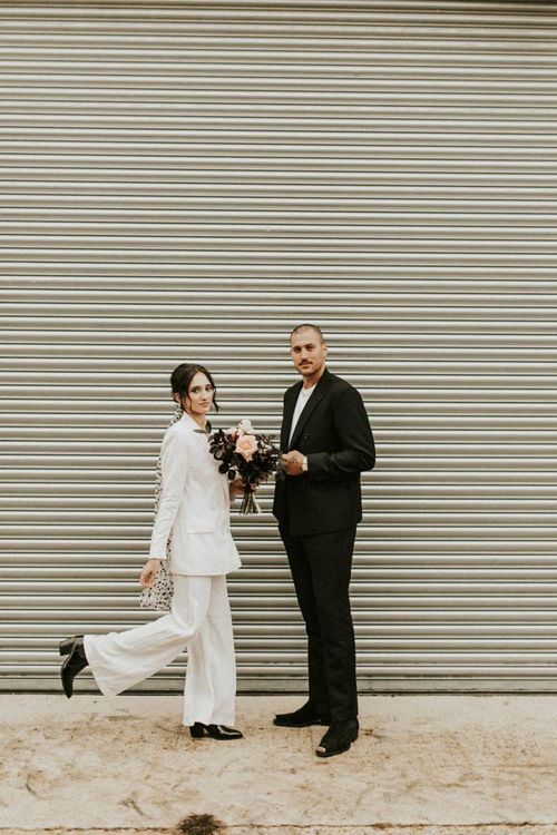 Stylish bride in trouser suit with groom in white t-shirt and blazer