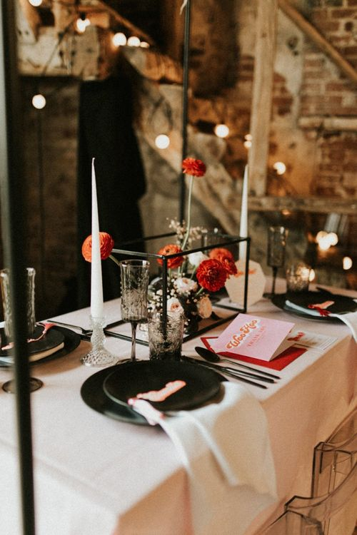 Black tableware and pink and red retro wedding stationery