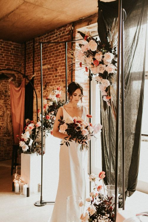 Bride in minimalist dress standing under a metal frame