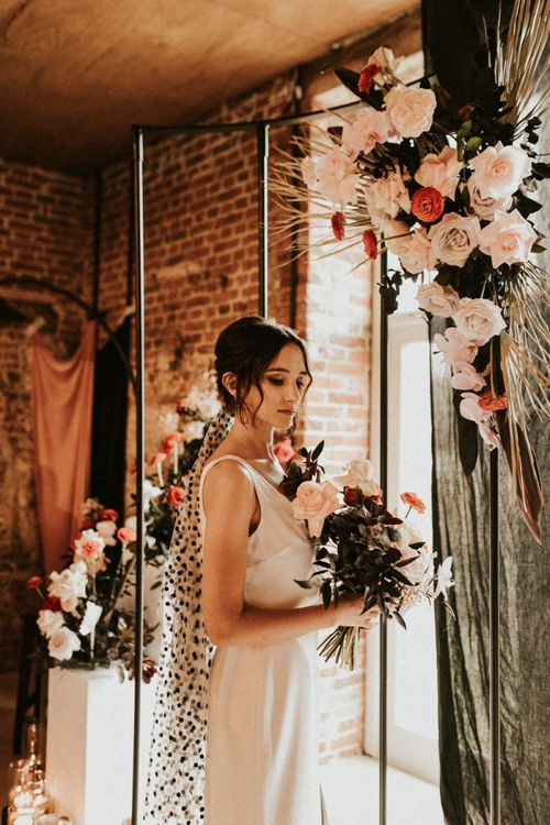 Stylist bride in minimalist wedding dress and black polka dot wedding veil
