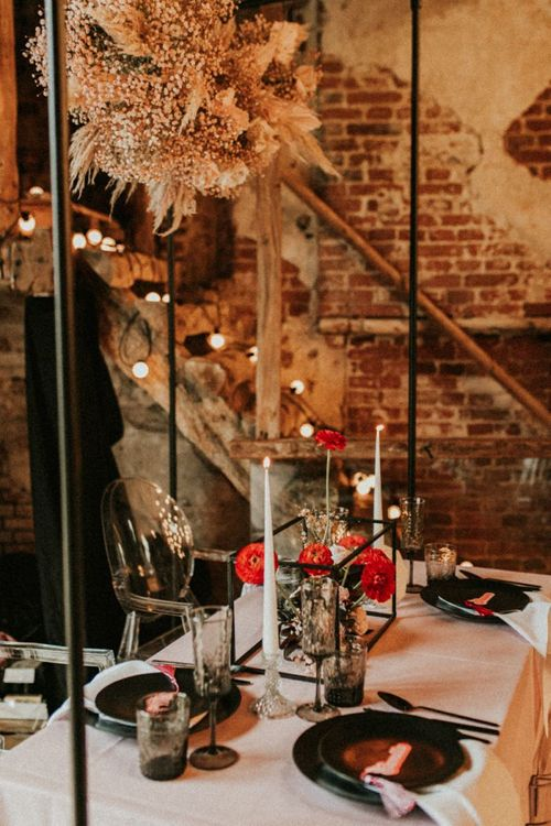Intimate wedding table with ghost chairs, retro stationery and hanging installation