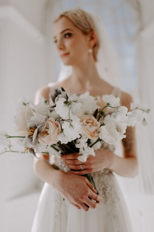 Modern wedding bouquet with open roses and ranunculus