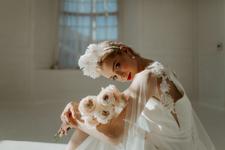 Beautiful bride in lace cape holding a pale pink bouquet for modern wedding ideas