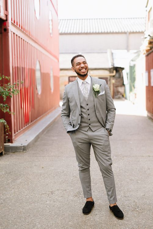 Groom Wears Grey Moss Bros Suit. Modern Warehouse Wedding in London at Trinity Buoy Wharf. Images by Captured by Katrina Photography