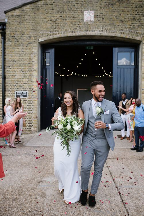 Contrasting Rose Petals for Confetti. Green Foliage and White Roses. Bride Wears Wed2b Dress. Modern Warehouse Wedding in London at Trinity Buoy Wharf. Images by Captured by Katrina Photography