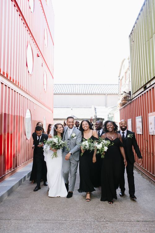 Monochrome Bridal Party Fashion. Bridesmaids in Black Boohoo Dresses. Bride in Wed2b. Groom in Grey Moss Bros. Groomsmen in Their Own Black Suits. Modern Warehouse Wedding in London at Trinity Buoy Wharf. Images by Captured by Katrina Photography