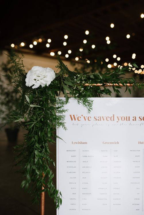 DIY Copper Arbour and Table Plan Stand.  Copper Foiled Table Plan. Green Foliage with White Roses and Copper Accents. Modern Warehouse Wedding in London at Trinity Buoy Wharf. Images by Captured by Katrina Photography