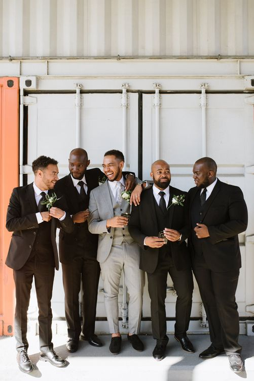 Monochrome Bridal Party Fashion. Groom in Grey Moss Bros. Groomsmen in Their Own Black Suits. Modern Warehouse Wedding in London at Trinity Buoy Wharf. Images by Captured by Katrina Photography