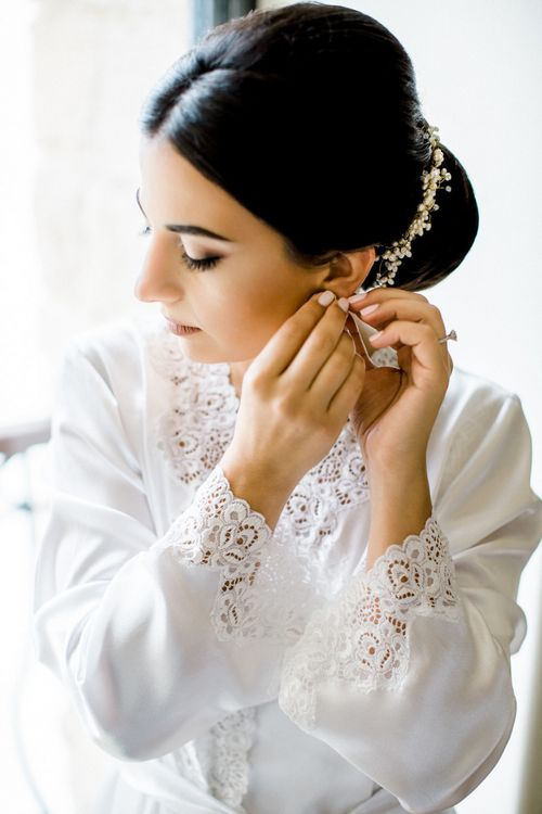 Bride in White Getting Ready Robe Putting on Her Earrings