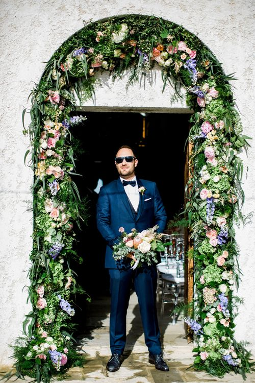 Groom Standing at Wedding Venue Entrance With Flower Arch Made Up Of Pastel Flowers and Foliage
