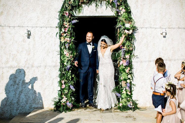 Bride and Groom Just Married Standing in From of Wedding Venue Entrance Decorated in Floral Arch
