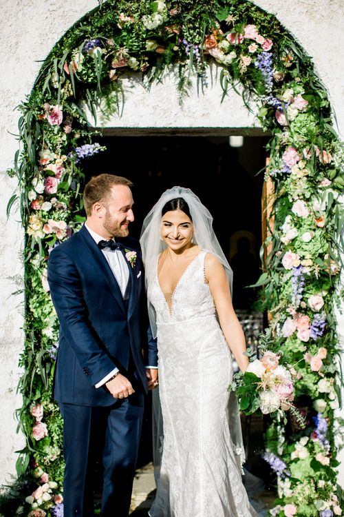 Bride and Groom Smiling Standing in From of Wedding Venue Entrance Decorated with Pastel Floral Arch
