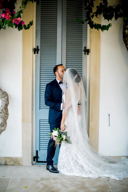 Bride in Lace  Anna Georgina Wedding Dress and Groom in Blue Suit  Embracing