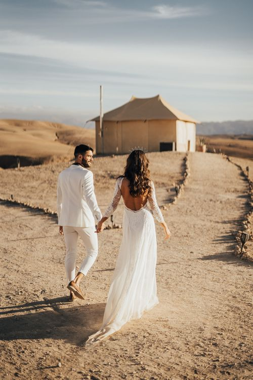 Bride in Grace Loves Lace Wedding Dress and Groom in White Suit Holding Hands