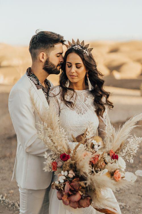 Bohemian bride and groom embracing at desert elopement