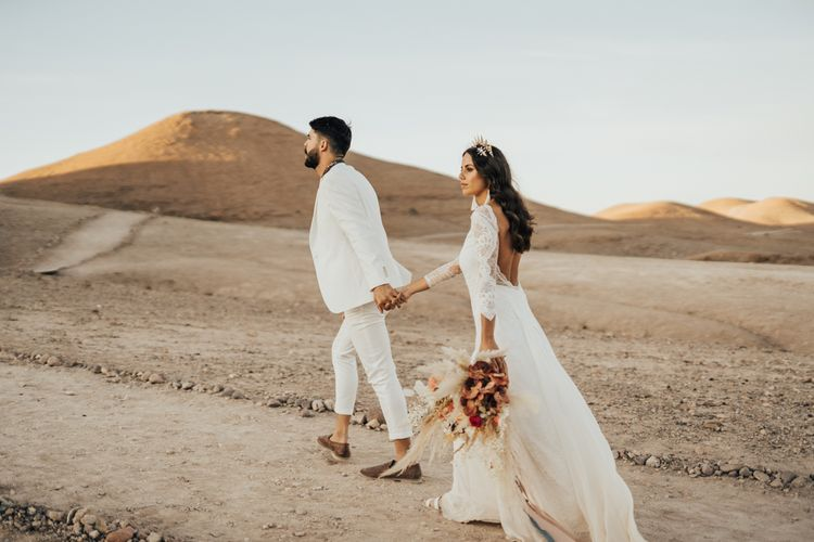 Bride and groom walking through the desert at their Moroccan wedding