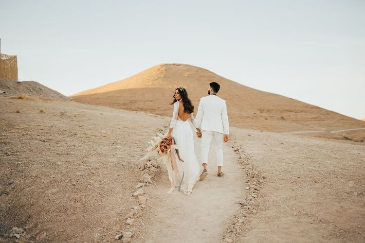 Bride in lace wedding dress and groom in white suit at desert elopement
