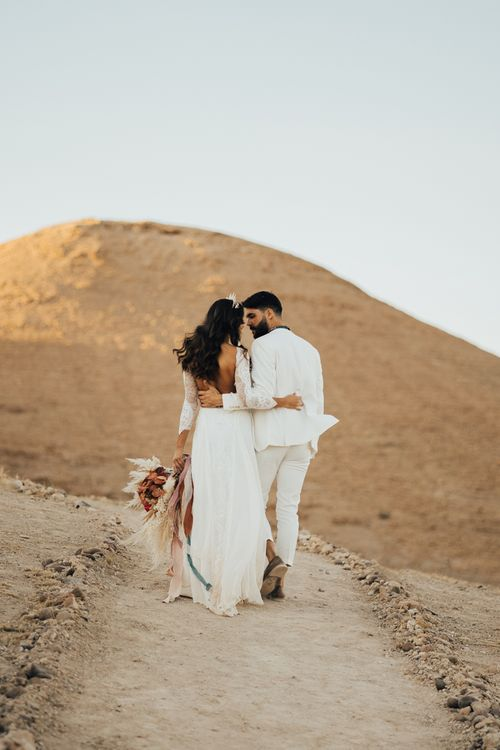 Boho bride and groom arm in arm at Moroccan wedding