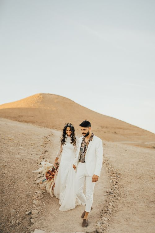 Stylish bride and groom holding hands at Moroccan wedding